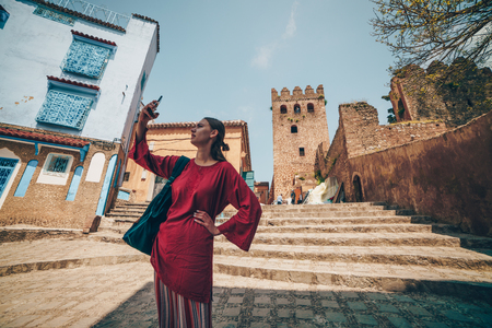 Girl traveler makes selfie on the background of the old city in Morocco, Chefchaouen 写真素材