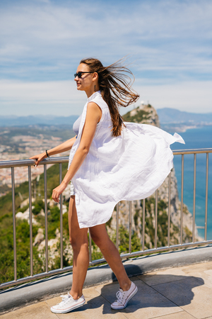 Girl traveler stands on the background of the rock of Gibraltar, looks into the distance 写真素材