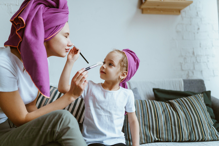 Mom and daughter do make-up and play after bathing