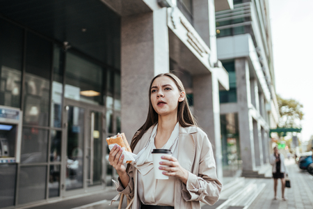 Hungry girl office worker hurries along the street and eats a sandwich on the go