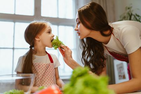 Moeder en dochter koken gezond eten, moeder voedt dochter met salade