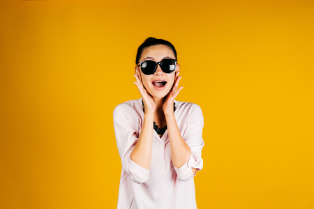 Surprised girl in black round glasses on a yellow background 写真素材