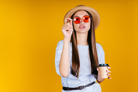A girl in a straw hat and round colored glasses drinks coffee and says something on a yellow background. 写真素材