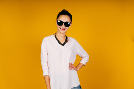 Cheerful woman in sunglasses on a yellow background
