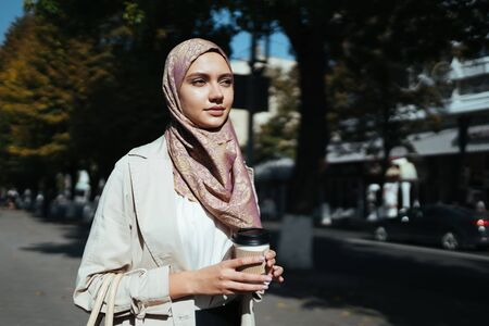 Young girl of oriental appearance with a scarf on her head holds a glass of coffee in her hands and goes to the business meeting in the city