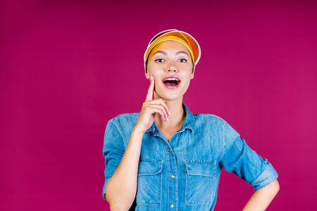 Wonderful young girl with dark hair braided in a ponytail and with the yellow cap on her head on a pink background in jeans shirt is surprised and admired