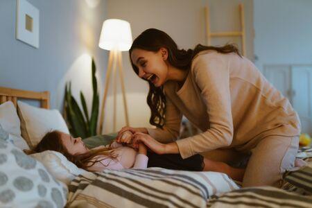 Jolie mère dans un pull beige chatouille et met au lit une petite fille dans la chambre Banque d'images