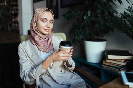 Wonderful young, oriental-looking business woman with a beige shawl on her head and in a gray jacket with a white blouse holds a cup of coffee in her hands and sits in the cafe