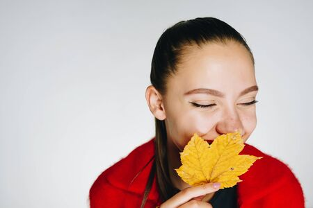 Charming young girl with long straight dark hair tied in a ponytail in a red jacket hides behind a yellow leaf and smiles on a white background