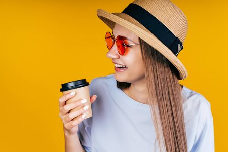 Charming girl with long straight brown hair with a straw hat on her head in orange sunglasses in a blue jacket holds a paper cup in her hands and smiles on the yellow background Stok Fotoğraf