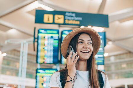 Charming young girl with long straight dark hair with a straw hat on her head in a white T-shirt talking on the phone near the schedule at the airport
