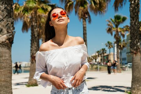 Charming girl with long brown hair in orange sunglasses in a white summer blouse and shorts stands on a background of palm trees and a sandy beach Stock Photo