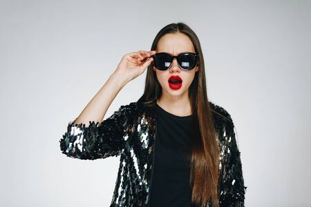 Fashionable girl with red lipstick on her lips. A girl with long hair in sunglasses, on the face of surprise and amazement. Shiny clothes, hand touches glasses, background in studio gray.
