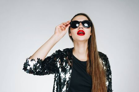 A fashionable long-haired brunette with red lipstick on her lips, opening her mouth in surprise, looks at a dump of glasses. Studio light gray, the clothes on the girl are shiny Stockfoto