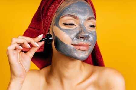 Charming young girl with a red towel on her head with a clay gray mask on her face and arrows holds the eyeliner cap on a yellow background and enjoys the mask