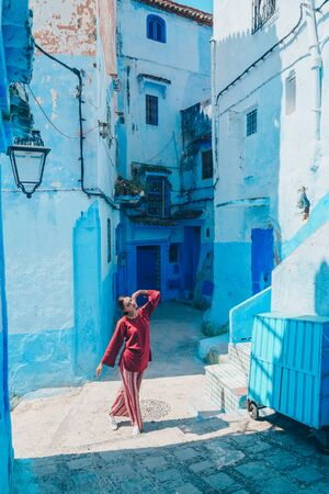 Wonderful young girl with bundled hair in a beard blouse and striped pants posing against a background of blue corridors of the eastern city Stock fotó