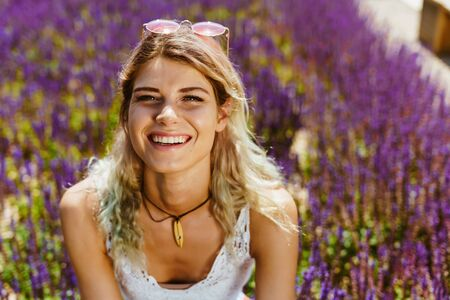 girl smiles at the sun on a background of blooming lavender Фото со стока