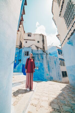 tourist in asian clothes on the streets of the blue city of morocco