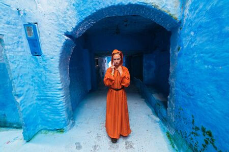 girl in Moroccan clothes in a blue city