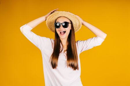 yellow background. girl emotionally joyfully exclaims opening her mouth in a hat and glasses