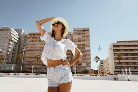 attractive european woman stands on the beach and with her head thrown back clings to the hat