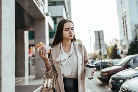 girl eats a hamburger on the go on the background of tall buildings and drinks coffee Banque d'images