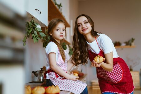 mom and little daughter baked pies in the kitchen