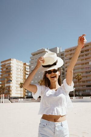 joyful girl on the beach exclaims in surprise, energetically lifting her hat and making a victory gesture with the other hand