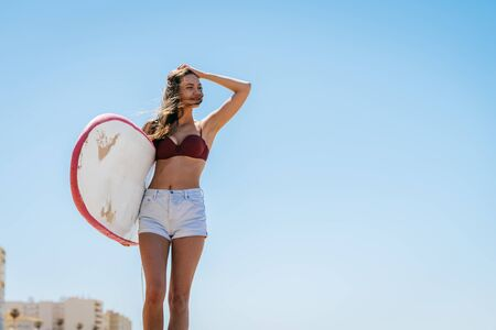 happy girl carries a surfboard on the beach