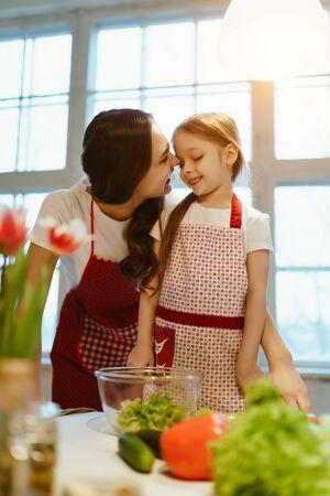 moeder en dochter in de keuken aan het kletsen en lachen