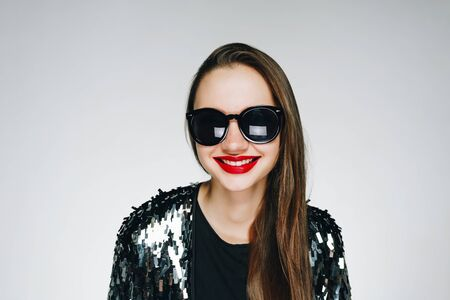 fashionable brunette with bright lipstick in sunglasses on a gray background smiles wide
