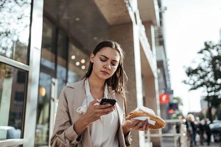 girl with fast food in hand holds typing numbers on the phone against the backdrop of the city Stockfoto
