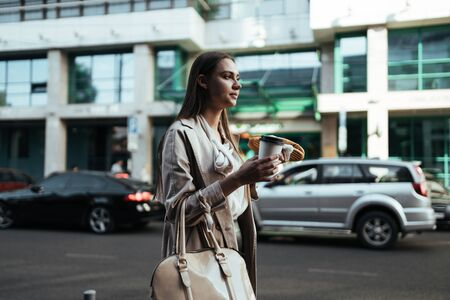 student walks down the street against the background of buildings and cars with coffee and a sandwich