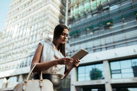 Un estudiante camina por la ciudad y mira una tableta.