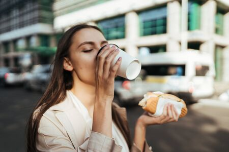 brunette on the street enjoys drinking coffee. in hand a pie Stockfoto