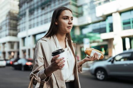 girl on the background of buildings, walks along the road and has a sandwich with coffee