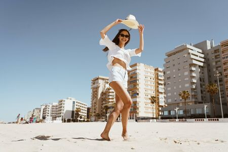 a beautiful girl cheerfully runs along the beach, lifting her hat above her head.