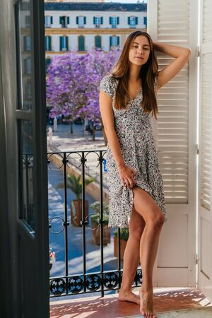 girl on vacation, stands by the open balcony and covered her eyes with satisfaction Фото со стока - 133680267