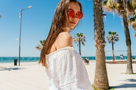 girl with wet hair looks through pink glasses on the background of the beach and palm trees