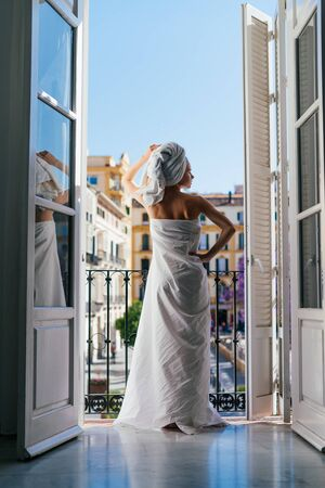 Woman relaxing in a hotel room on a balcony in a sheet and a towel on her head stands with her back to the camera against the background of a European city Фото со стока - 133680613