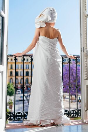 Woman relaxing in a hotel room on a balcony in a sheet and a towel on her head Фото со стока - 133680611