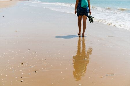 a barefoot figure is walking along the coastal sand. view from the back 写真素材