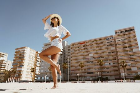 happy girl dancing on the beach against the background of the city