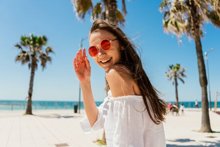 brunette woman with a smile wrapping herself over her shoulder kindly waves her hand 写真素材