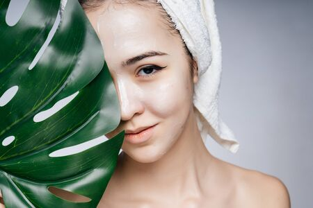 An Asian woman in a towel on her head covered half her face with a sheet of monstera, her shoulders are bare Фото со стока - 133680762