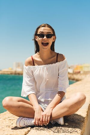 brunette woman sitting lotus position, opened her mouth with an exclamation of joyful surprise against the background of the sea 写真素材