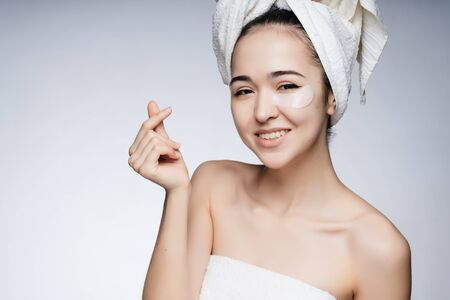 an Asian woman glues patches under her eyes, her hair is covered with a towel, her body is decorated with a sheet Stock Photo