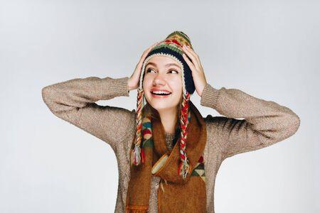北の人々の暖かい帽子をかぶった少女が、彼女の手に頭を抱え、喜んで微笑む
