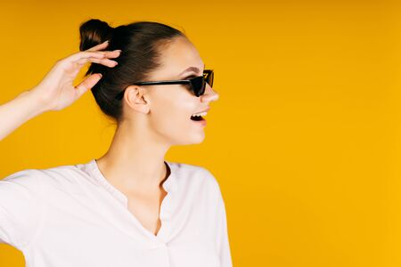 a girl in profile with her hair gathered in a bun in black glasses with a silly look opened her mouth and scratches her head with her hand