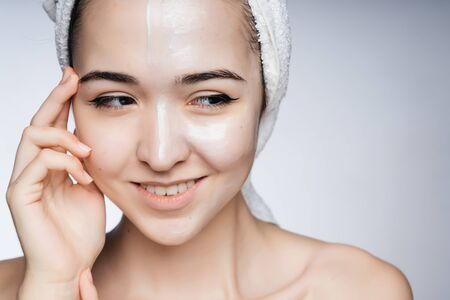 Asian after a shower with a towel on her head smiling gently squinted her eyes to the side Фото со стока - 133680947
